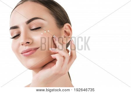 Close up of face and hand of young happy woman putting dots of cream on her cheek with closed eyes. She is enjoying using cosmetics. Copy space in right side. Isolated