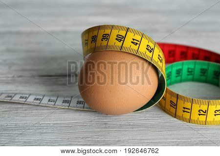 Egg with measuring tape on wooden table