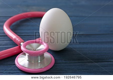 Egg with stethoscope on wooden table