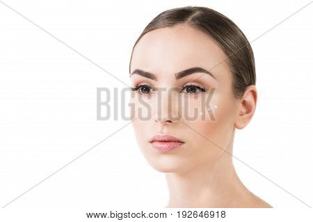 Portrait of young pensive woman looking to distance. She is wearing natural make-up and three dots of cream on cheek. Isolated and copy space in left side