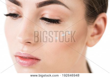 Close up of face of young pensive beautiful woman with three dots of cream on her cheek and eyes half closed. She is wearing decorative cosmetics on. Isolated