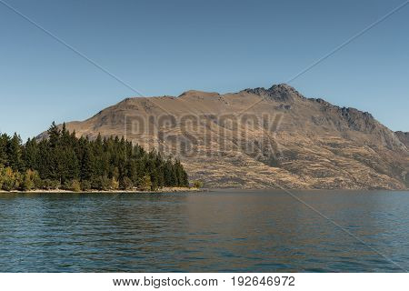 Queenstown New Zealand - March 15 2017: Brown mountain range with Cecil Peak across dark blue Wakatipu Lake and downtown under lighter blue sky. Part of green forest fronts the mountain.