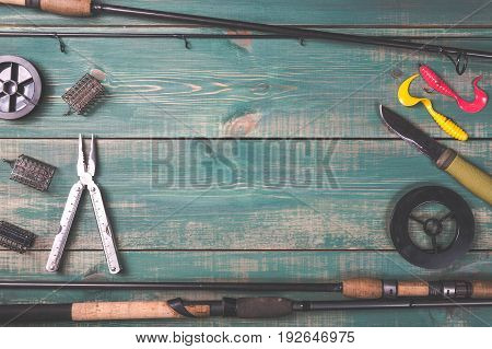 Fishing rods, fishing tackles, lines, knife and feeders on green wooden background with free space.
