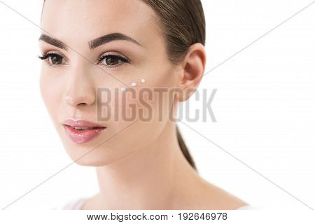 Portrait of jolly young woman with natural make-up. She is having dots of cream on her cheek and looking to distance in deep thoughts. Isolated and copy space in right side