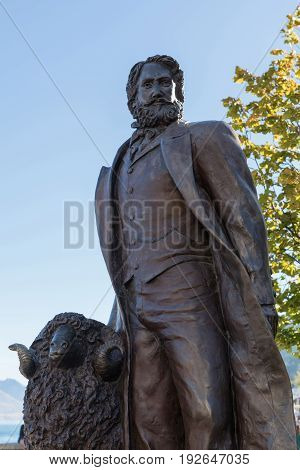 Queenstown New Zealand - March 15 2017: closeup of dark bronze statue of William Gilbert Rees city founder in downtown against blue sky with some green foliage in back. Sheep holds him company.