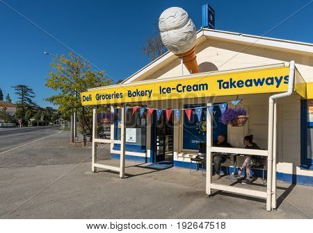 Lawrence New Zealand - March 15 2017: The grocery store in the small town sells mainly food and household items. Big ice cream cone and people on the patio. Blue sky and street scene.