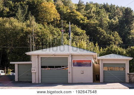 Lawrence New Zealand - March 15 2017: The volunteer fire station in the small town of Lawrence with closed doors offers space for one fire engine. Green trees background.