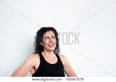 Incredulous woman looks up into blank white space where copy can go. She has her hands on her hips and is almost laughing as she looks like she can not believe what she is seeing.