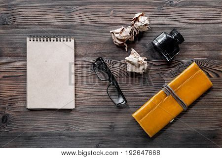 Writer acsessories. Vintage notebook, feather pen, crumpled paper on white background top view.