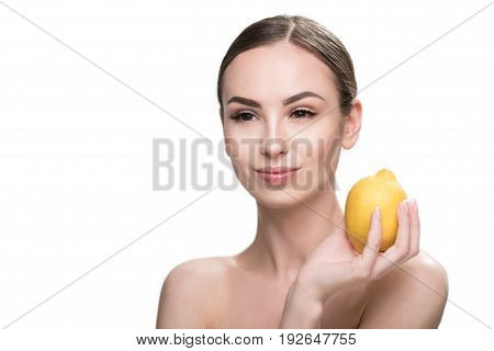 Portrait of cheery young woman with naked shoulders holding lemon in one hand aside her face. She is wearing light make-up. Isolated and copy space in left side