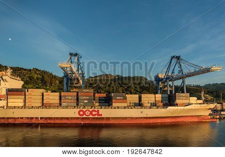 Port Chalmers New Zealand - March 15 2017: The loaded OOCL Dalian container ship is docked. Lateral view. Early morning light with forested hills in back. Blue sky with moon.