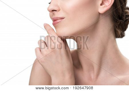 Close up of lower face and neck with palm of happy young woman. She is slightly touching her chin by hand and smiling with joy. Isolated