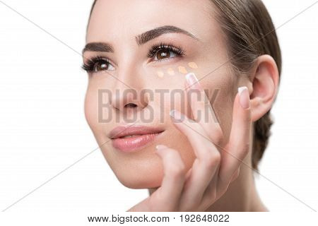 Close up of face and hand of happy young woman applying dots of foundation by fingers under her eye. She is looking aside to distance with pleasure. Isolated