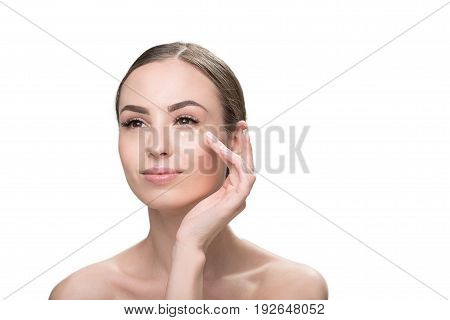 Portrait of happy young lady putting base dots on her face under eyes. She is applying cosmetic by her finger. Isolated. Copy space in right side