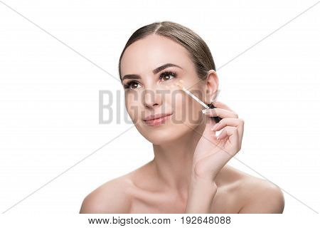 Portrait of jolly young woman applying foundation dots under her eye by fiber tipped applicator. Isolated