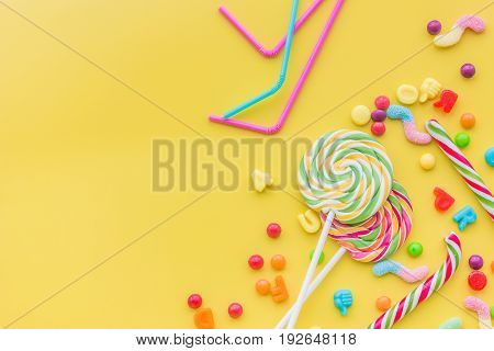 Sweets for birthday including lollipop and drops on yellow background top view copyspace.