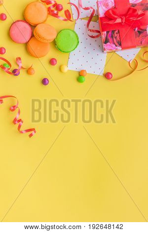 Birthday concept with wrapped gift and sweets on yellow background top view copyspace.