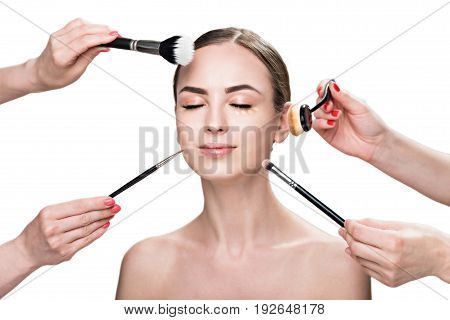 Portrait of happy attractive girl with closed eyes. She is being applied different types of visage cosmetic in beauty salon by various brushes. Isolated