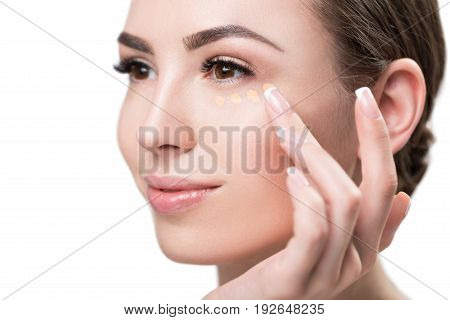 Close up of face and hand of jolly young woman applying foundation dots by fingers under her eye. Isolated