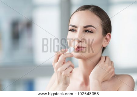 Portrait of pensive young woman applying lip-gloss and keeping her other hand by neck. She is touching lips by lipstick and looking to distance with admiration. Copy space in left side