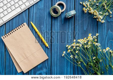 flowers and home office materials on bright blue desk background flat lay space for text