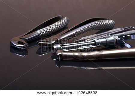 Set of metal medical equipment tools for teeth dental care on black mirror background. Selective focus