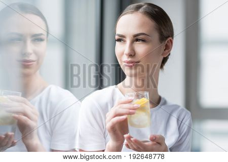Jolly young woman with perfect make-up is standing with glass of lemonade in her hands nearby huge window. She is looking with joy through her reflection into it