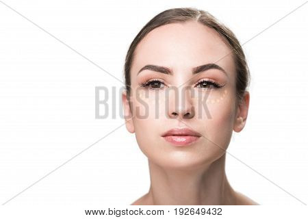 Foundation is on female face. Round drops of cream under eyes. Portrait. Isolated and copy space