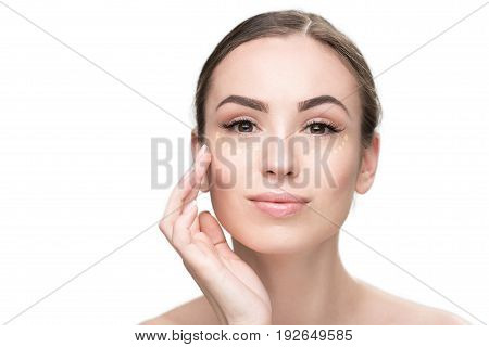 Attentive young lady is using foundation in order to make her face more beautiful. She looking at camera with smile. Portrait. Isolated
