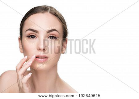 Confident lady has drops of foundation on her face. She touching to lips and looking at camera with curiosity. Portrait. Isolated and copy space
