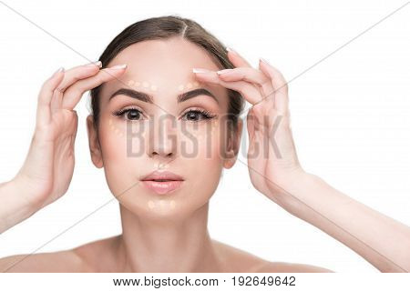 Confident woman is applying concealer on face and looking at camera with sensuality. Portrait. Isolated