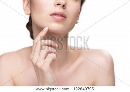 Sensual woman with perfect skin doing base make-up. She carefully touching to her chin. Close up. Isolated