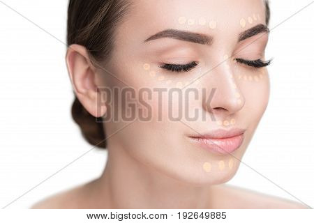 Attractive woman is closing her eyes. She presenting beige foundation. Portrait. Isolated