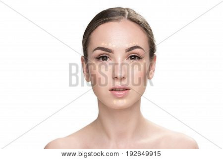 Confident woman is applying beige foundation and looking at camera with interest.
