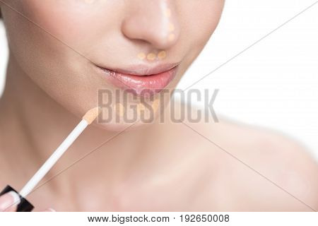 Soigne lady is using make-up brush for applying beige foundation. Close-up of female chin. Isolated