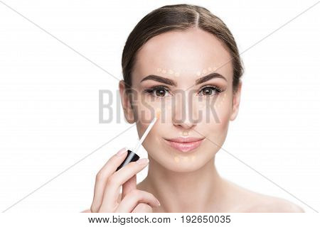 Cheerful young lady is holding make-up brush and applying beige concealer. Portrait. Isolated and copy space