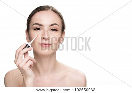 Happy girl is applying foundation through special brush and looking at camera with light smile. Portrait. Isolated and copy space
