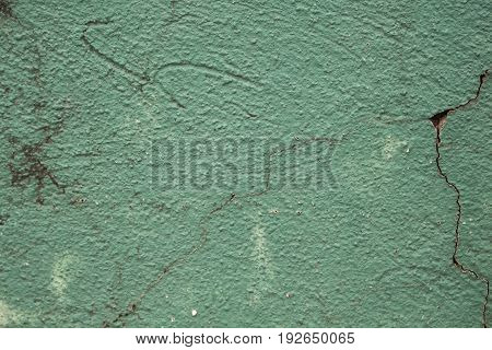 Green painted wall with cracks photo texture. Cement wall with stains and grit closeup. Rustic old surface for vintage background. Teal paint on plaster background. Rough concrete wall close-up image