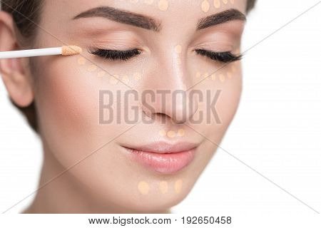 Lovely young woman is doing make-up through foundation, applying with brush. Portrait. Isolated