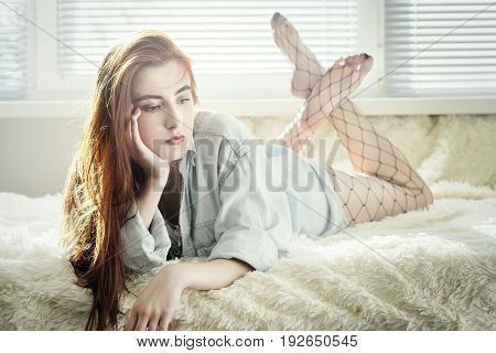 sensual beautiful woman lying at sofa with blinds light in sunlight