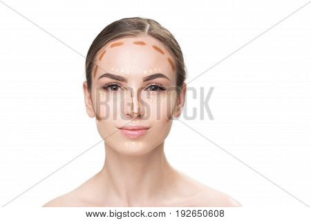 Confident woman has light and brown concealers on her face. She looking at camera with interest. Portrait. Isolated