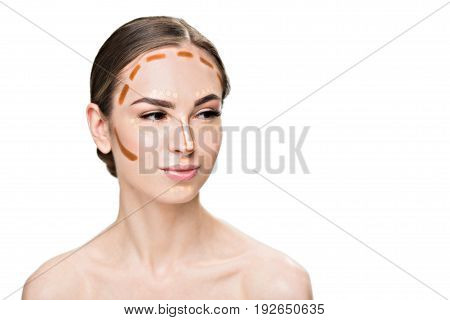 Attractive young woman is using concealers in order to make her face more beautiful. She looking aside with light smile. Portrait. Isolated and copy space