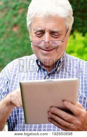 Old Man Using Digital Tablet.