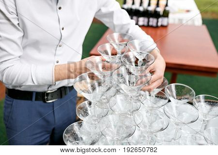 Waiter builds a pyramid of glasses for champagne at outdoor garden in wedding ceremony