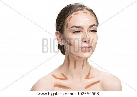 Attractive young lady is using various concealers in order to create perfect make-up. Portrait. Isolated and copy space