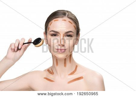 Confident pretty lady is holding special brush for creating facial features and directly looking at camera. Portrait. Isolated