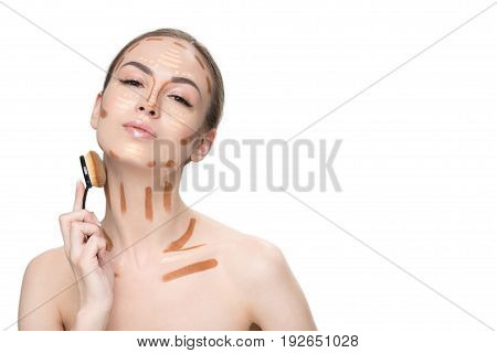 Attractive woman is creating perfect tone of face through special brush. She has various correctors on visage. Portrait. Isolated and copy space