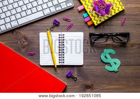 Money for education concept. Dollar sign, notebook and keyboard on wooden table top view.