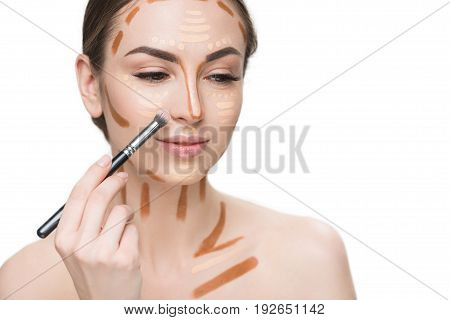 Beautiful young lady is using brush for creating right tone of skin. She has various concealers on visage. Portrait. Isolated and copy space