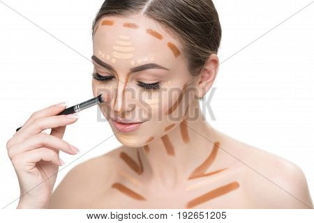 Confident young lady is using cosmetic brush in order to create perfect tone of skin. She has various concealers on face and clavicles. Portrait. Isolated